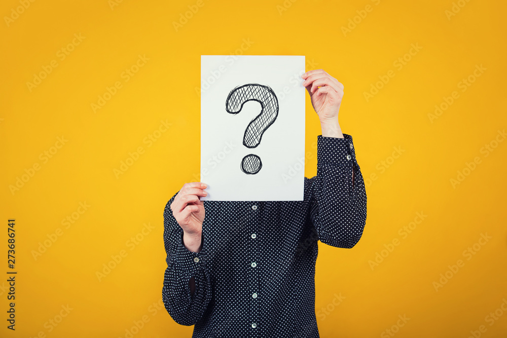 Fototapeta Businesswoman covering face using a white paper sheet with drawn question mark, like a mask, for hiding her identity. Isolated on yellow wall background