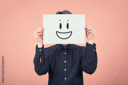Businesswoman covering face using a white paper sheet with smile emoticon sketch, like fake mask for hiding identity and real emotion from society. Introvert female anonymity concept