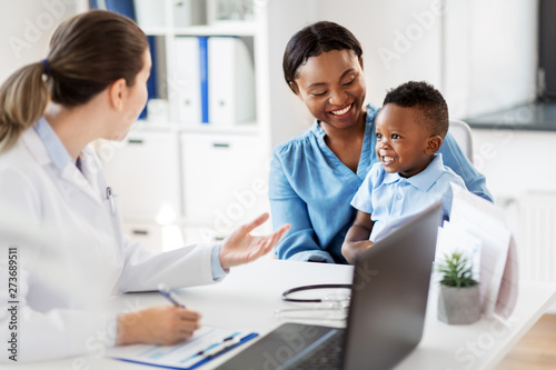 medicine, healthcare and pediatry concept - happy african american mother with baby son and caucasian doctor at clinic - 273689511
