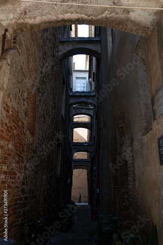 Alley with stone arches. Albenga, Italy. Wallpaper Mural