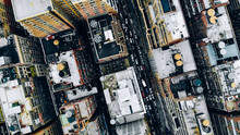 Aerial View Of New York Downtown Building Roofs With Water Towers. Bird's Eye View From Helicopter Of Cityscape Metropolis Infrastructure, Traffic Cars Moving On City Streets And District Avenues