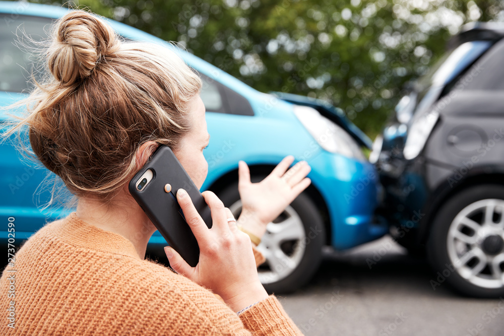Fototapeta Female Motorist Involved In Car Accident Calling Insurance Company Or Recovery Service