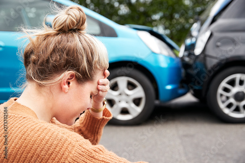 Fotografía  Female Motorist With Head In Hands Sitting Next To Vehicles Involved In Car Acci
