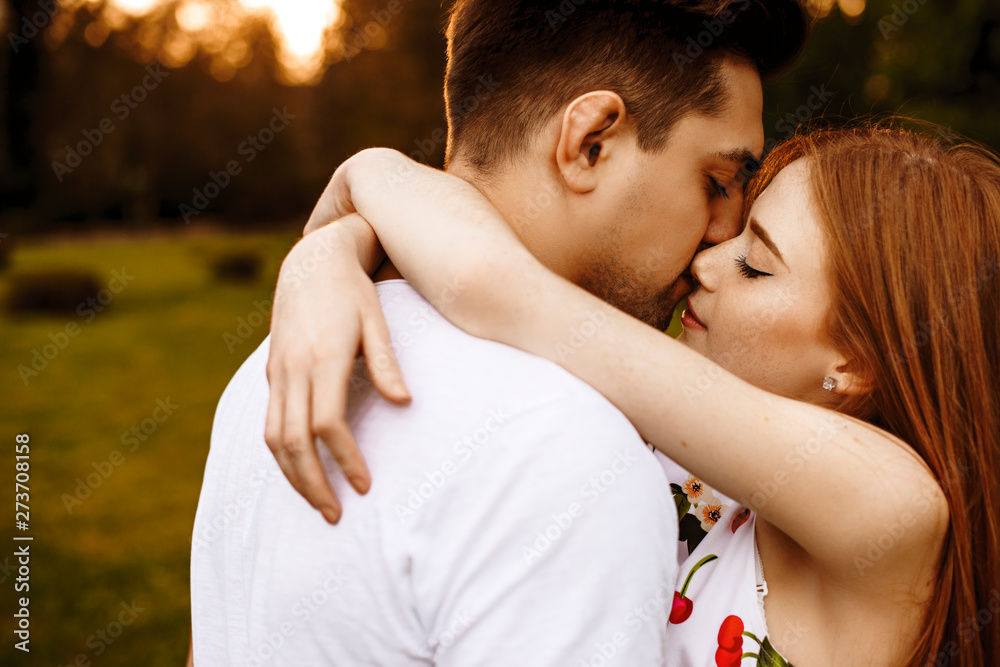 Fototapeta Side view portrait of a beautiful young caucasian couple embracing and kissing outside while dating against sunset.