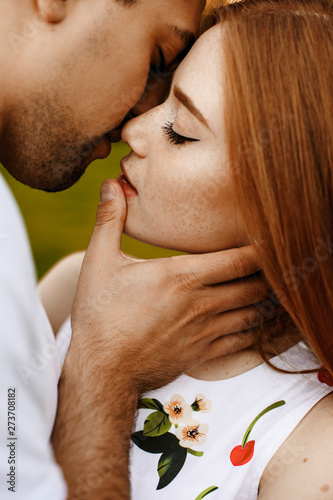 Fototapeta Close up portrait of a lovely red haired female with freckles kissing with her man with closed eyes closed while man is touching her on the lips. obraz