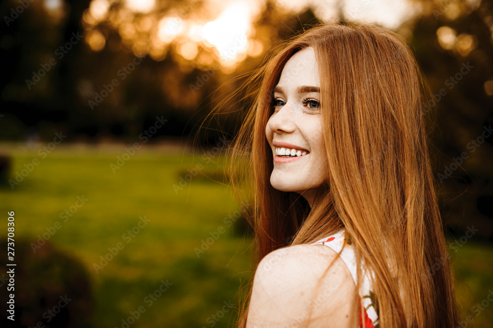 Fototapety, obrazy: Portrait of a lovely female with long red hair and freckles looking away laughing against sunset outside.