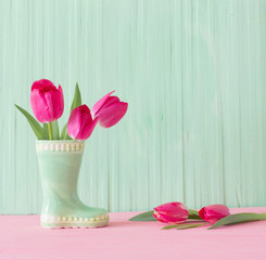 pink tulips in vase on wood...