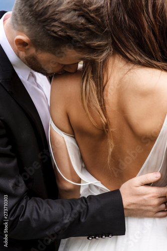 Obraz Back view of a beautiful bride being kissed by her groom on the shoulder. - fototapety do salonu