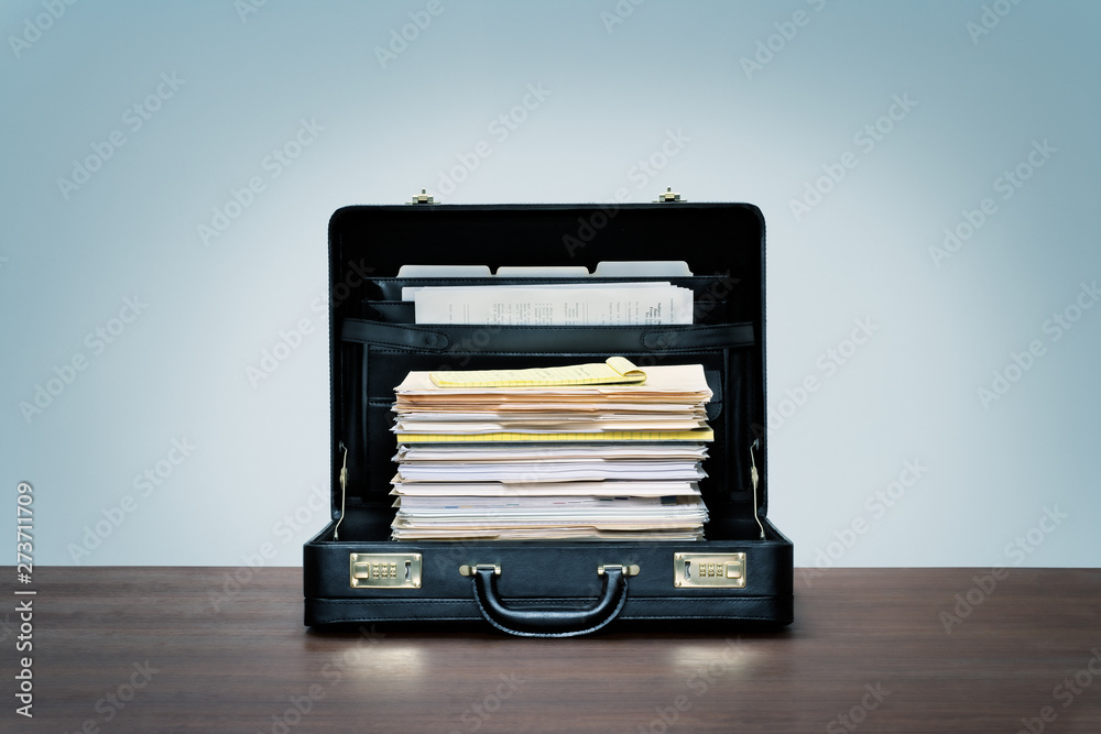 Fototapeta Tall stack of files and folders in black leather briefcase on wood desk with blue background.