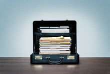Tall Stack Of Files And Folders In Black Leather Briefcase On Wood Desk With Blue Background.