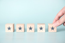 Woman Hand Putting Wooden Five Star Shape On Blue Background. Best Excellent Services Rating For Satisfaction.