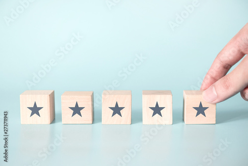 Tela Woman Hand putting wooden five star shape on blue background