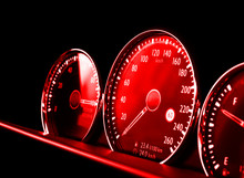 Close Up Shot Of A Red Speedometer In A Car. Car Dashboard. Dashboard Details With Indication Lamps.Car Instrument Panel. Dashboard With Speedometer, Tachometer, Odometer. Car Detailing.
