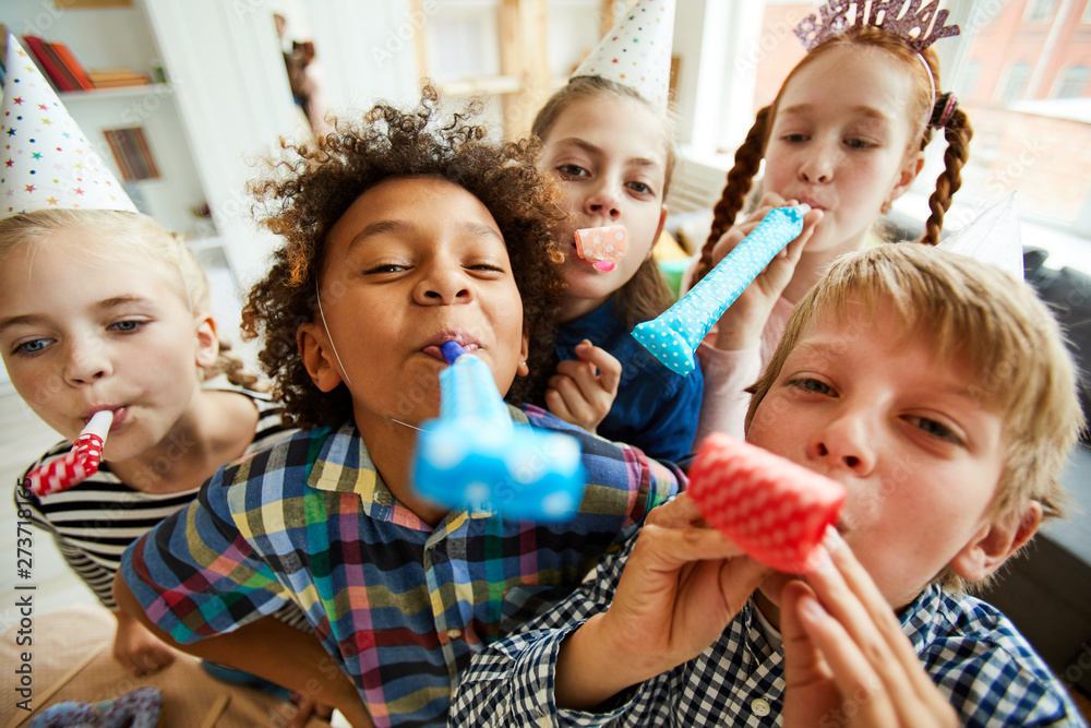 Fototapety, obrazy: High angle view at multi ethnic group of children blowing party horns at camera