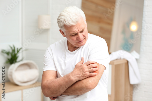 Senior man scratching arm indoors. Allergy symptom Wallpaper Mural