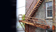 Old Rusty Fire Escape Stairs On Brick Building