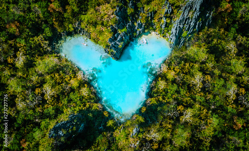 Photo Aerial top view of turquoise lagoon shaped heart inside of tropical island