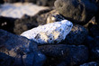 Close up of isolated bright white rock on pile of black rocks on beach in evening sun - El Cotillo, Fuerteventura