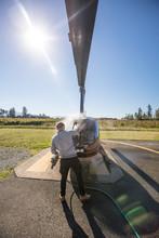 Rear View Of Pilot Washing His...