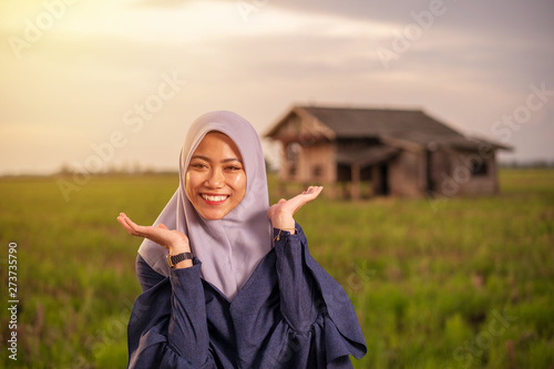 Fotomural  Close up portrait of happy young pretty Asian woman in hijab with paddy field meadow background and traditional house