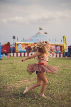 Girl Spins Excitedly As A Circus Rolls Into Town.