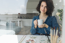 Pensive Brunette Woman Artist Sitting At Table With Cup Of Coffee And Looking Away In Workplace