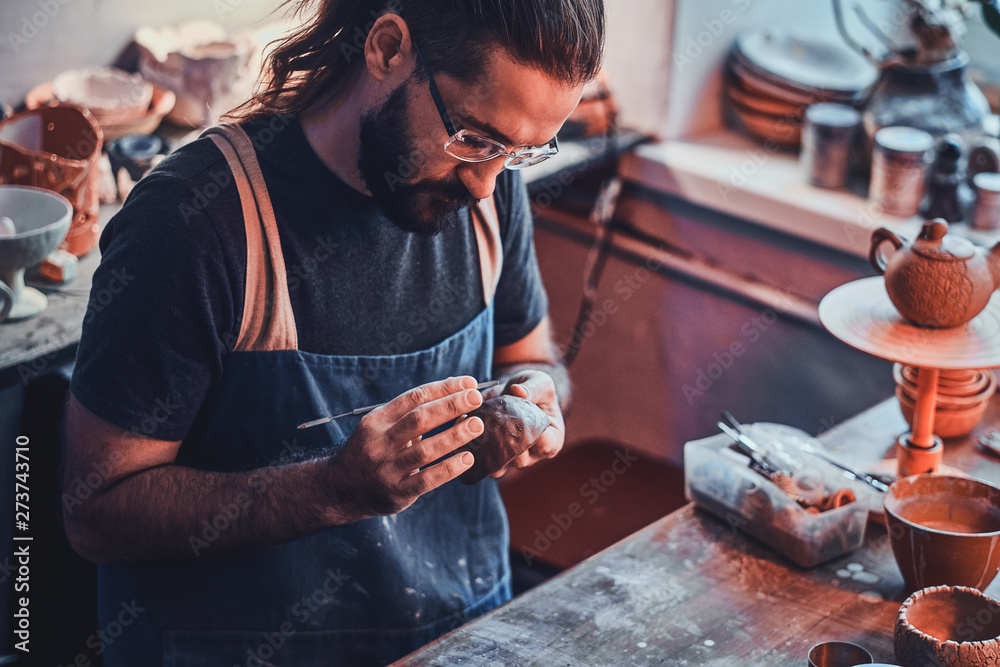 Fototapety, obrazy: Diligent pensive man in glasses at his pottery workshop is workig for new project.