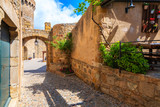 Fototapeta Uliczki - Narrow street and castle gate in historic old town of Tossa de Mar, Costa Brava, Spain