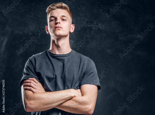Young arrogant male is looking to the camera crossed his hands over dark background Wallpaper Mural