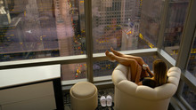 COPY SPACE: Unrecognizable Woman Sits In A Leather Chair And Observes The City.