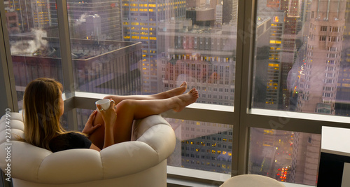CLOSE UP: Unrecognizable woman sits in a leather chair and observes the city.