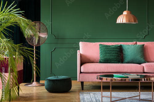 Copper lamp and table in a green living room interior. Real photo - 273749307