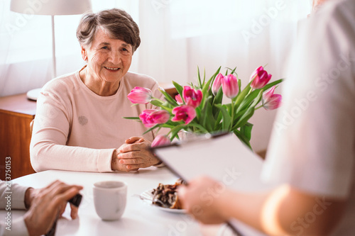Foto  Smiling senior lady listening to her doctor in the nursing home