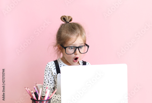 Litttle girl lookinLitttle girl looking at laptop screen with expression of surprised and excitement. Smart, smilling little girl taking notes . Communication in business concept.