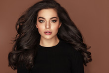 Brunette Haired Woman Portrait With Blue Eyes And Healthy Long Shiny Wavy Hairstyle. Volume Shampoo. Black Curly Permed Hair And Bright Makeup.  Beauty Salon And Haircare Concept.