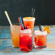 Variety summer drinks with citrus and berries.