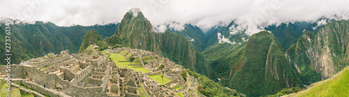 Fototapeta Top panoramic view of the upper town in Machu Picchu ancient city ruins with Huayna Picchu and the whole green valley on the background