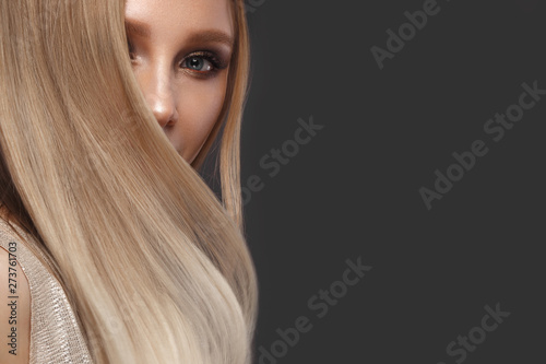 Fotografía Beautiful blond girl in move with a perfectly smooth hair, and classic make-up