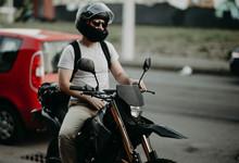 Man Enduro Motorcycle Driver In The City. Biker In A Helmet.
