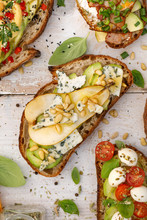 Open Sandwiches, In The Middle Of Board An Open Avocado Sandwich Made Of Slice Of Sourdough Bread With The Addition Of Pear, Blue Cheese, Nuts And Honey, Top View, Close-up