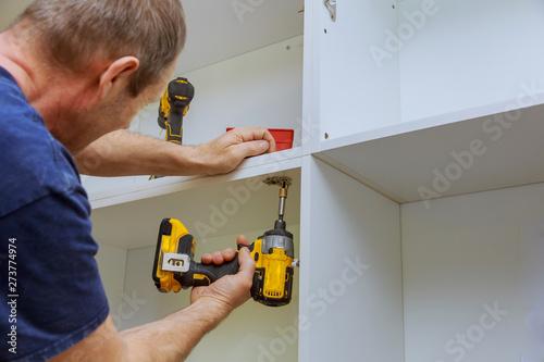 Obraz na plátne  Assembling furniture white in modern kitchen screws using screwdriver