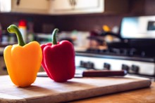 Red Pepper And Yellow Pepper And Knife On On A Wooden Board