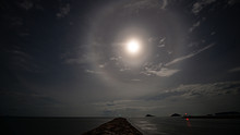 Stunning Beautiful Big Lunar Ring And Bright Moon In Little Cloudy Sky Night Floating Over Seascape Stock Photo