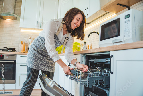 Photo young pretty woman putting dishes in dishwasher