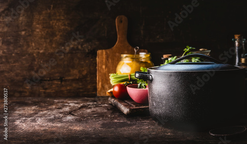 Obraz na płótnie Cast iron pot with fresh herbs, spices and kitchen utensils for tasty cooking on rustic table