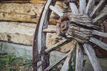 Old Wooden Wagon Wheel With A Rusty Chain Wrapping Around One Of The Spokes