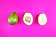Leinwanddruck Bild - Cut avocado on a pink background. The concept of vegetarianism, healthy eating, organic food rich in vitamins. Minimalism, top view, flat lay. Copy space. Design, summer concept.