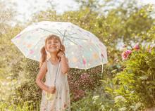 Happy Little Girl In Garden Under The Summer Rain With An Umbrella.
