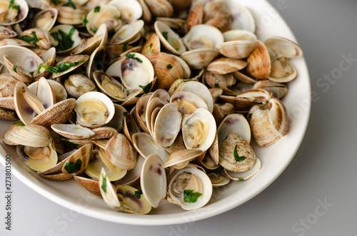 Steamed clams in garlic sauce in a white bowl. Close-up Tapéta, Fotótapéta