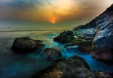 Sunset Or Golden Hours By The Sea Side Or Beach, A Long Exposure Shot, Water Touching The Rocks In The Water Slowly